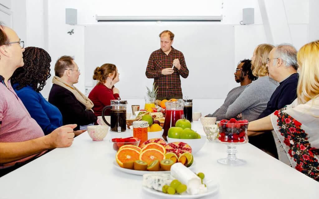 Människor sitter runt ett bord dukat med en härlig frukost
